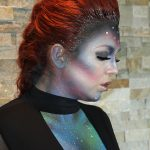 Female model with red hair in up-do of french braid down middle and glitter accents with alien makeup on face