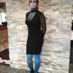 Full body shot of female model in black dress, alien makeup on legs and face