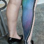 Detail shot of alien makeup and zipper detail going up female model's leg