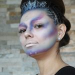 Female model with up-do hairstyle, glitter accents and tight cornrow braids on sides with alien makeup on her face