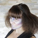 Female model with dark brown hair puffed out with glitter highlights in alien makeup on her face