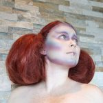 Female model with red hair puffed out with small braid details in alien makeup on her face