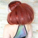 Female model with red hair puffed out with small braid details in alien makeup on her back
