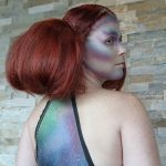 Female model with red hair puffed out with small braid details in alien makeup on her face and back