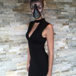 Body shot of female model with up-do hairstyle wearing black dress and in alien makeup that includes a zipper opening down her face